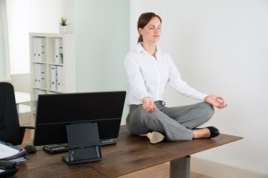Young Businesswoman Doing Yoga On Wooden Desk In Office